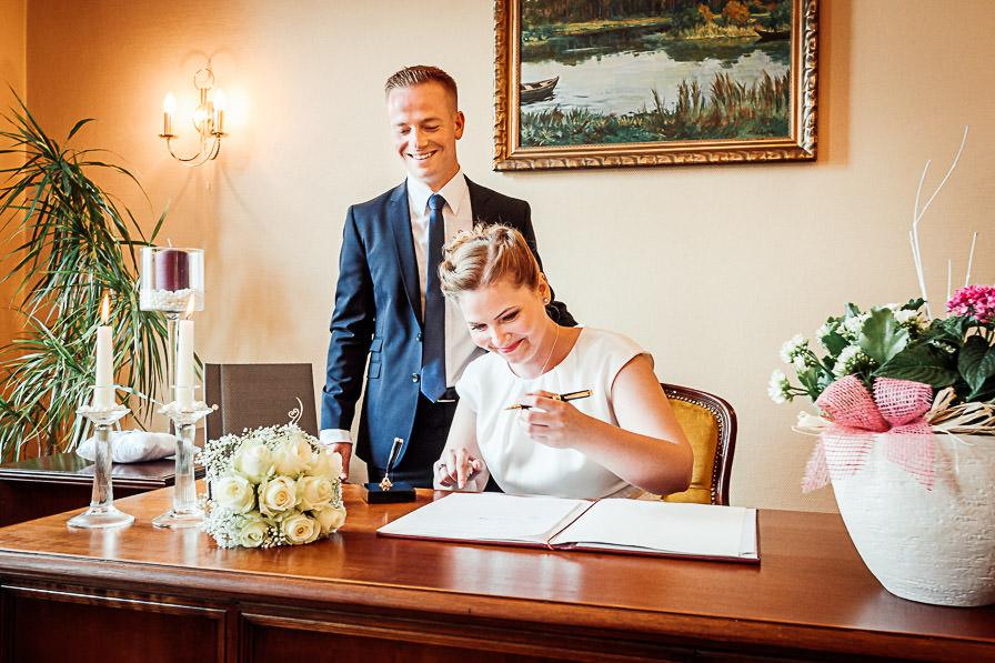Standesamtliche Trauung mit der Braut bei der Unterschrift im Standesamt