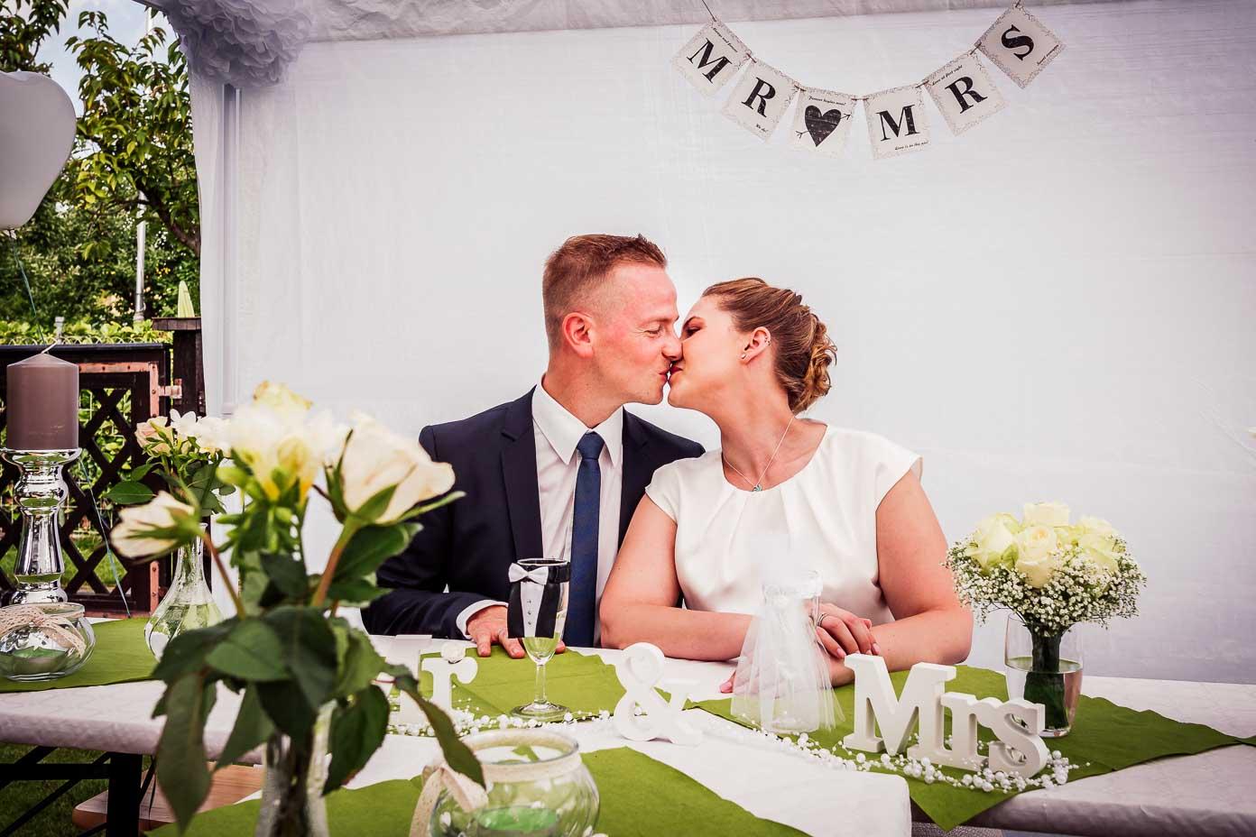 Das Brautpaar küsst sich bei der Gartenparty