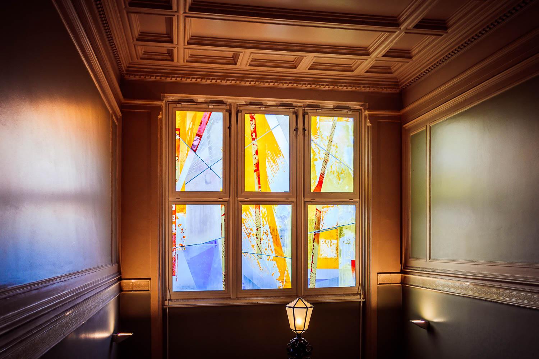Buntes Fenster im Treppenhaus des Standesamtes Neukölln
