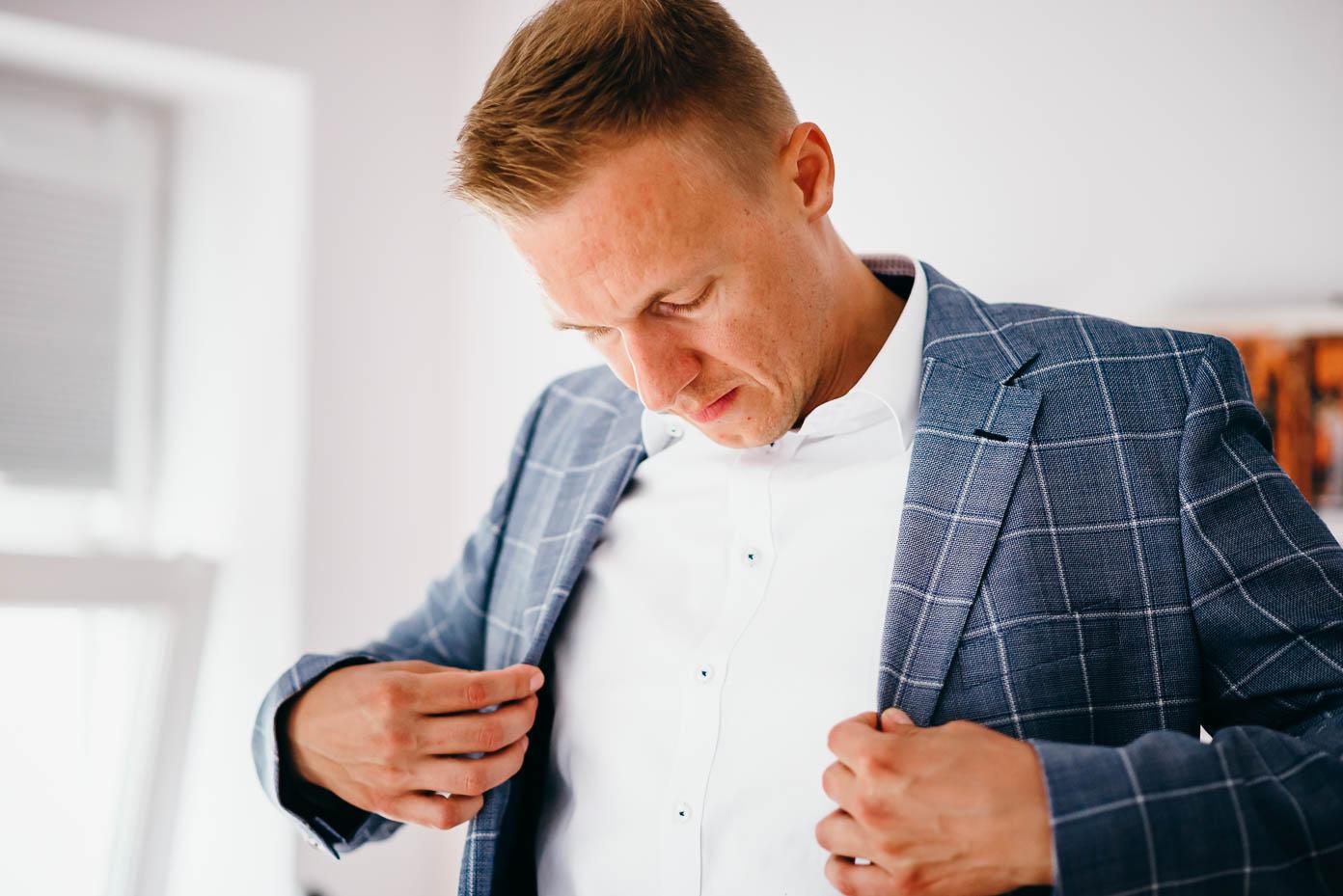 Der Bräutigam zieht sein Sakko an.