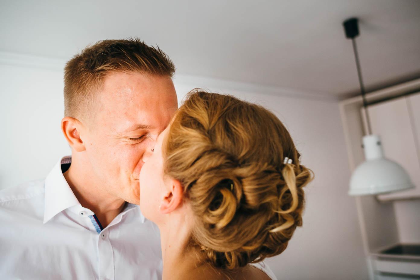 First Look - Braut und Bräutigam küssen sich.