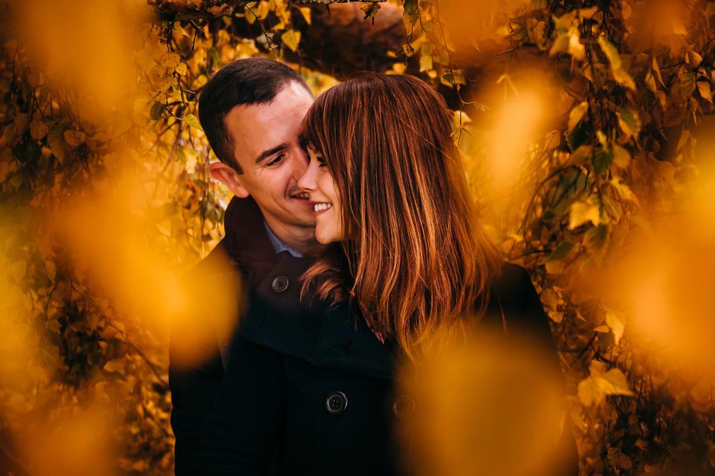 Paar hinter Blättern im Herbst