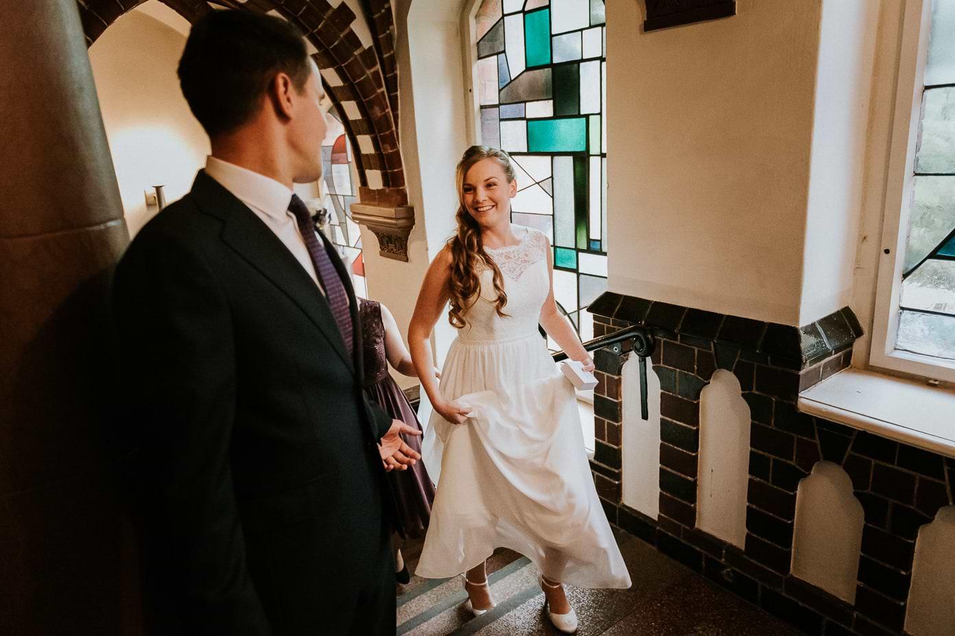 Das Brautpaar schreitet die Treppe im Standesamt hinauf