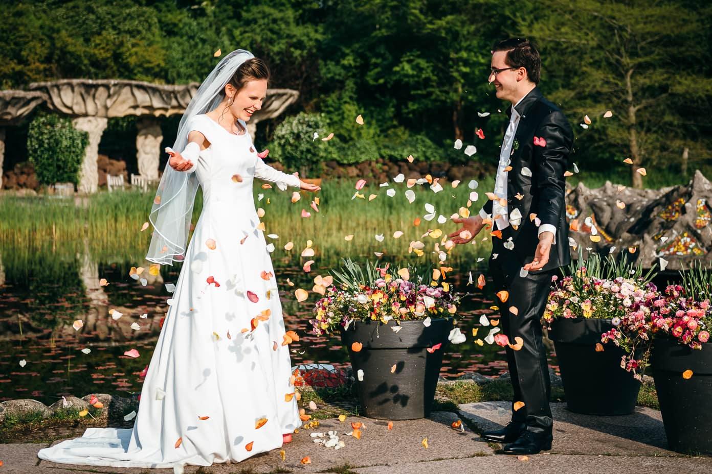 Brautpaar mit Blütenblättern (Rosen)