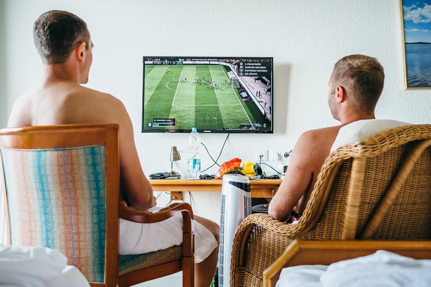Bräutigam und Trauzeuge zocken Playstation am Morgen