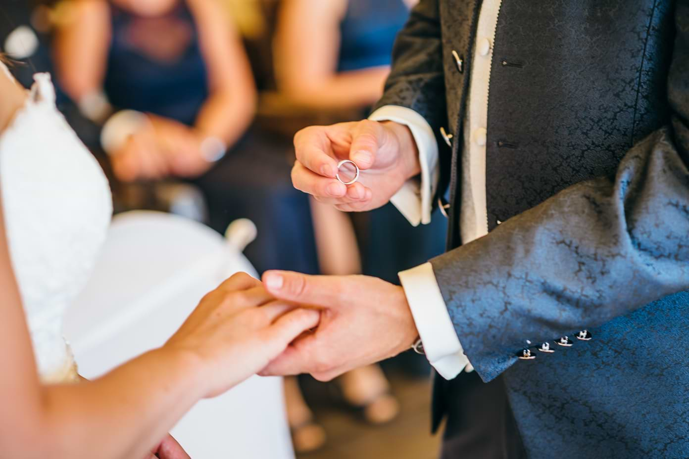 der Bräutigam steckt der Braut den Trauring an die Hand