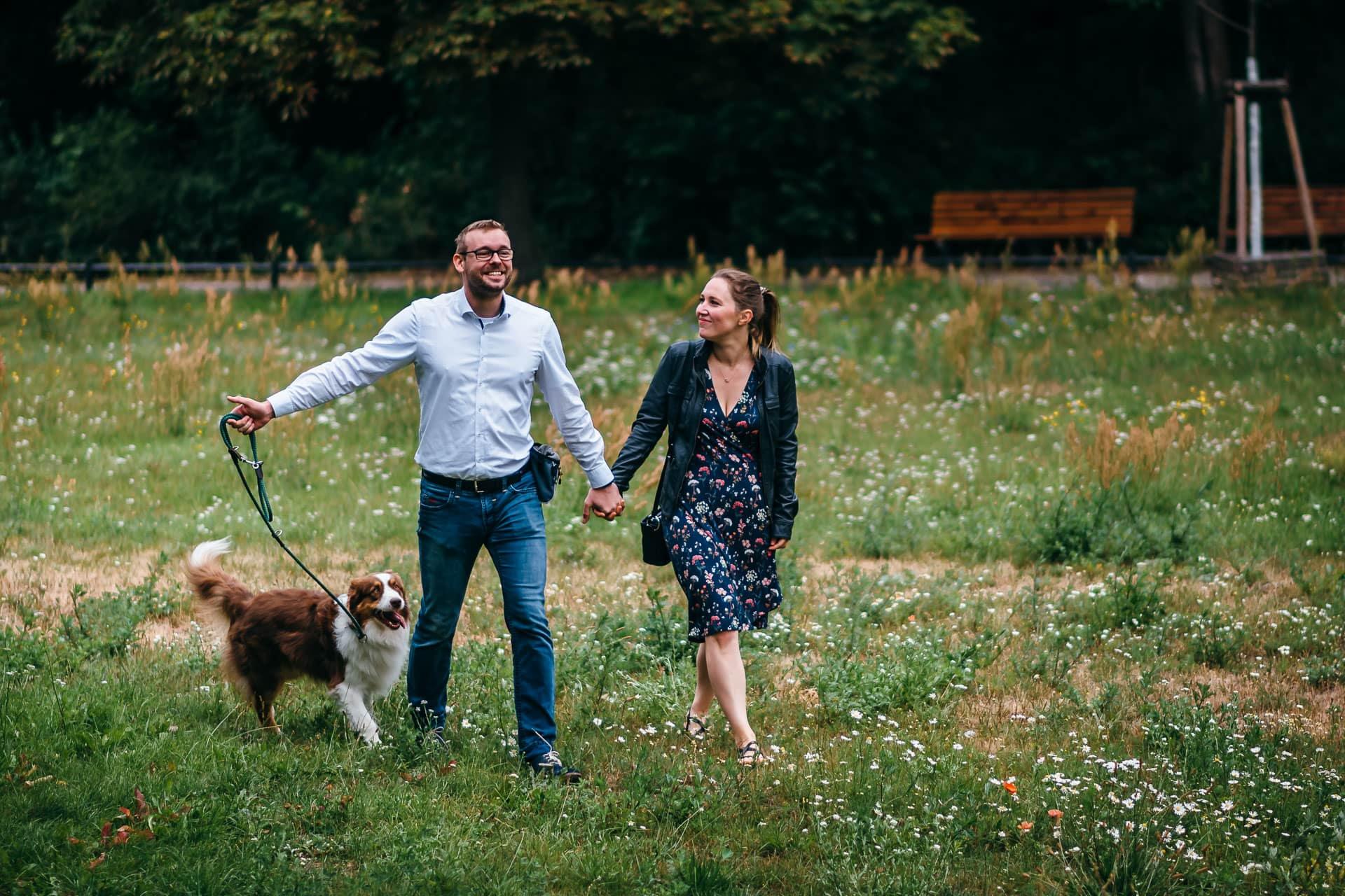 Paar mit seinem Hund auf einer Wiese im Schlosspark Buch
