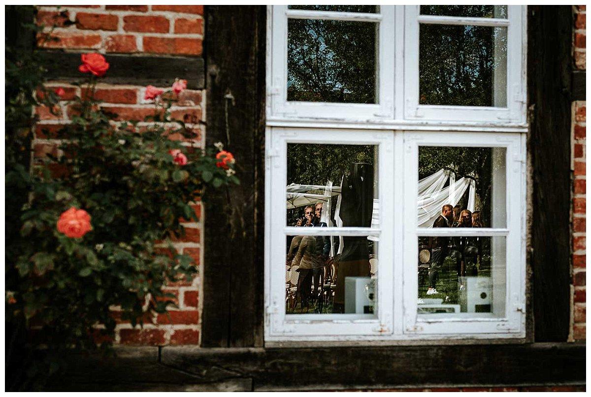Spiegelung der Hochzeitsgesellschaft im Fenster