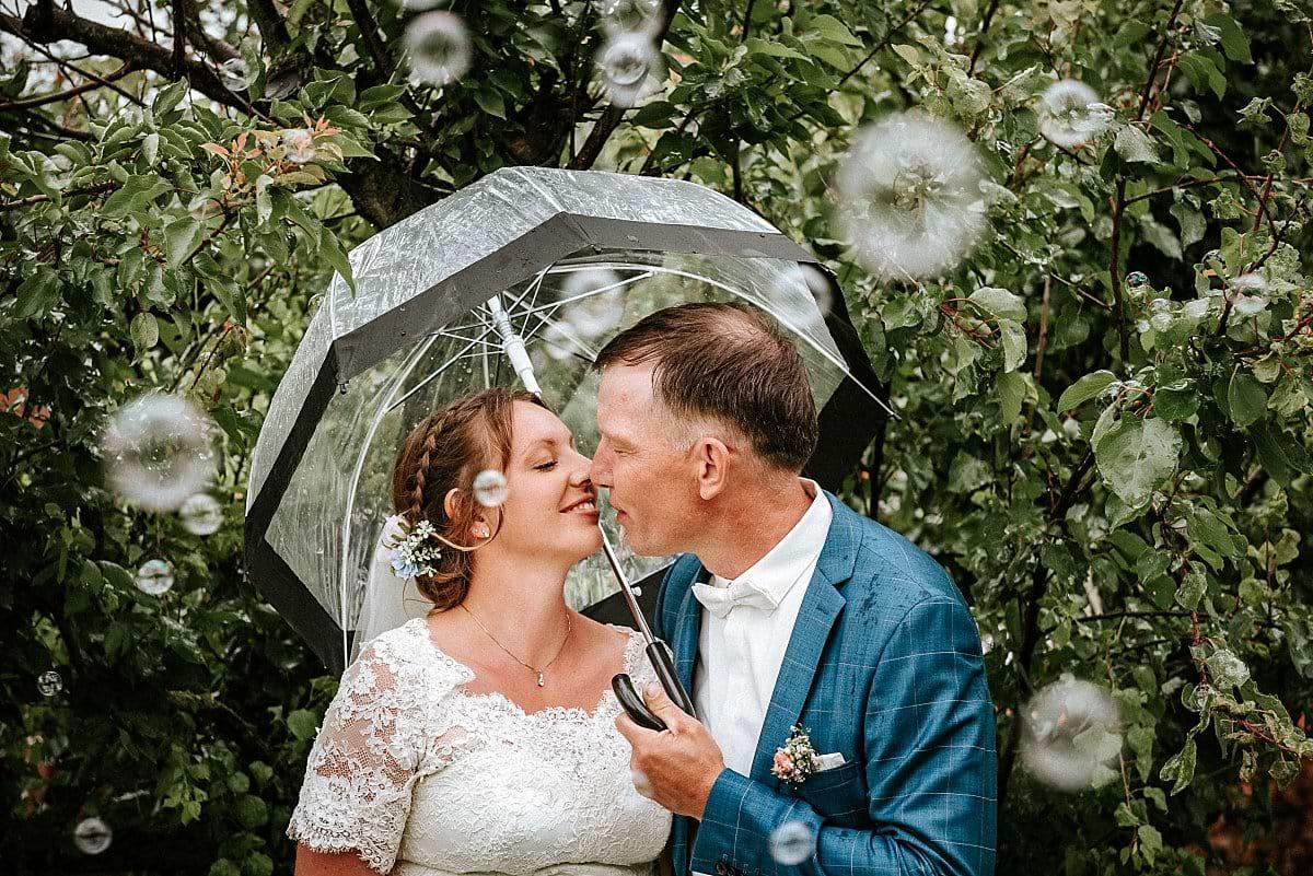 Brautpaar unter Regenschirm